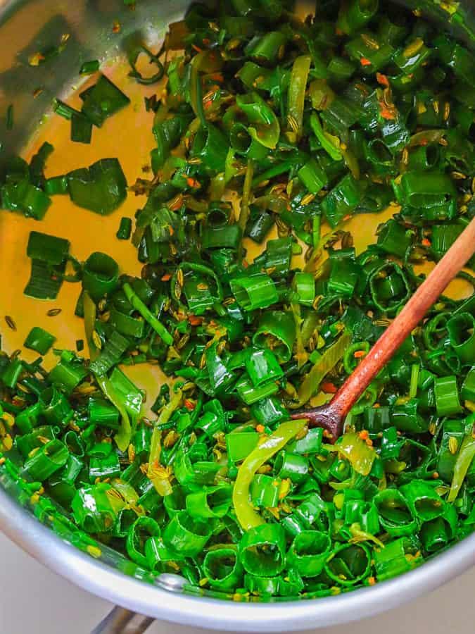 Cuisson des oignons et des épices avec des oignons verts dans une casserole