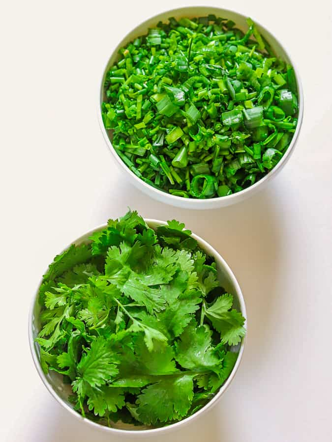 Fresh cilantro leaves & diced chives in white bowls