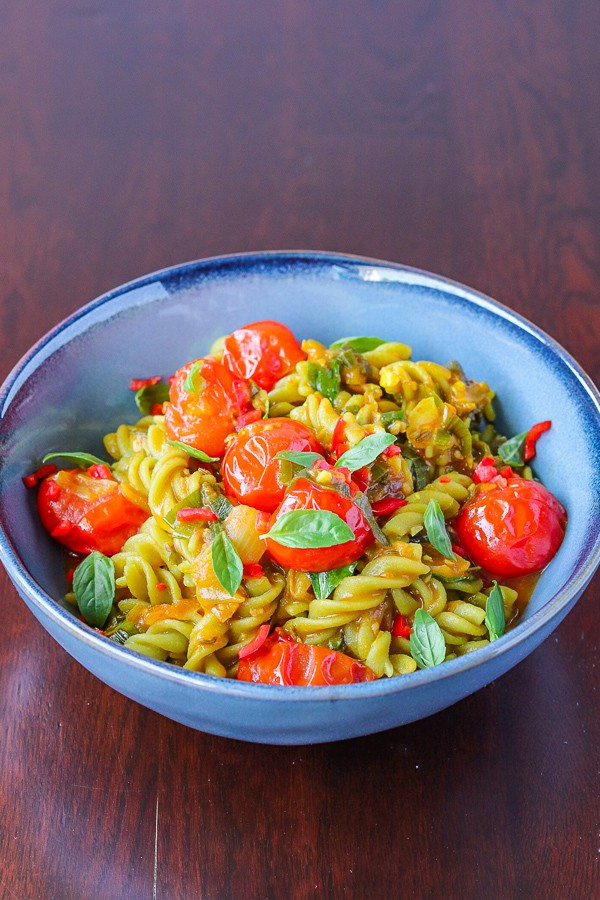 served pea pasta, basil & cherry tomatoes in a bowl