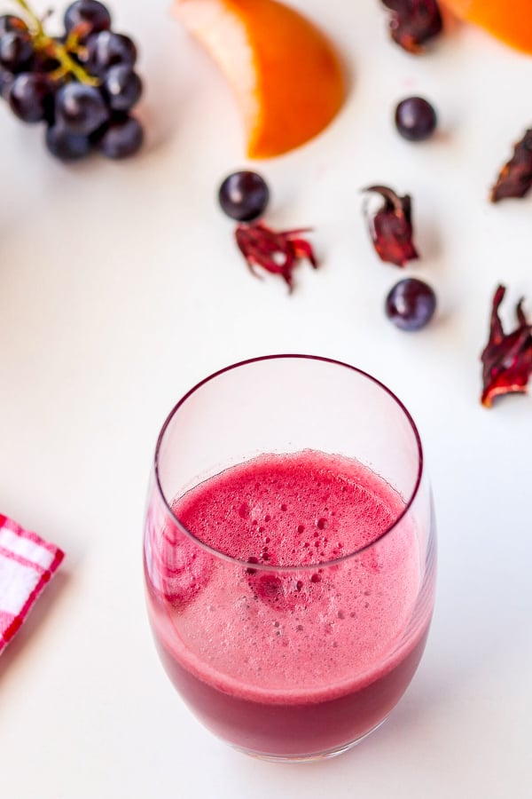 a glass of freshly made grapefruit juice with hibiscus & grapes