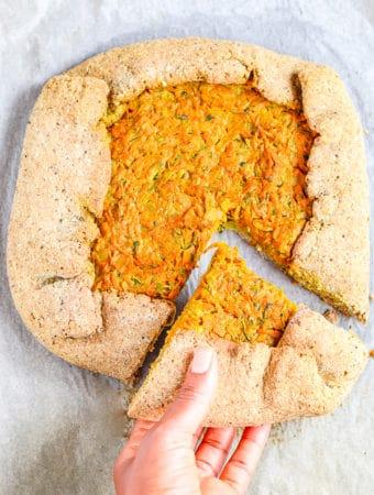 holding a slice of vegan vegetable galette