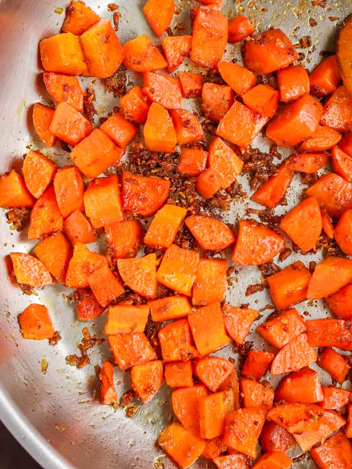 Diced carrots cooking in cumin spice