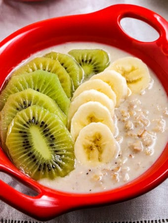 vegan overnight oats with kiwifruit in a red bowl