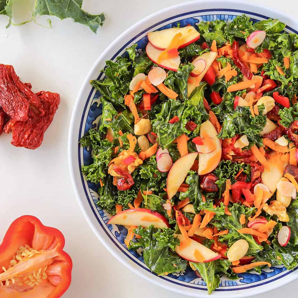 A kale salad recipe with sun-dried tomatoes in a plate
