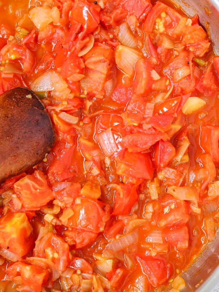 onions and tomatoes cooking in a pan with a wooden spoon