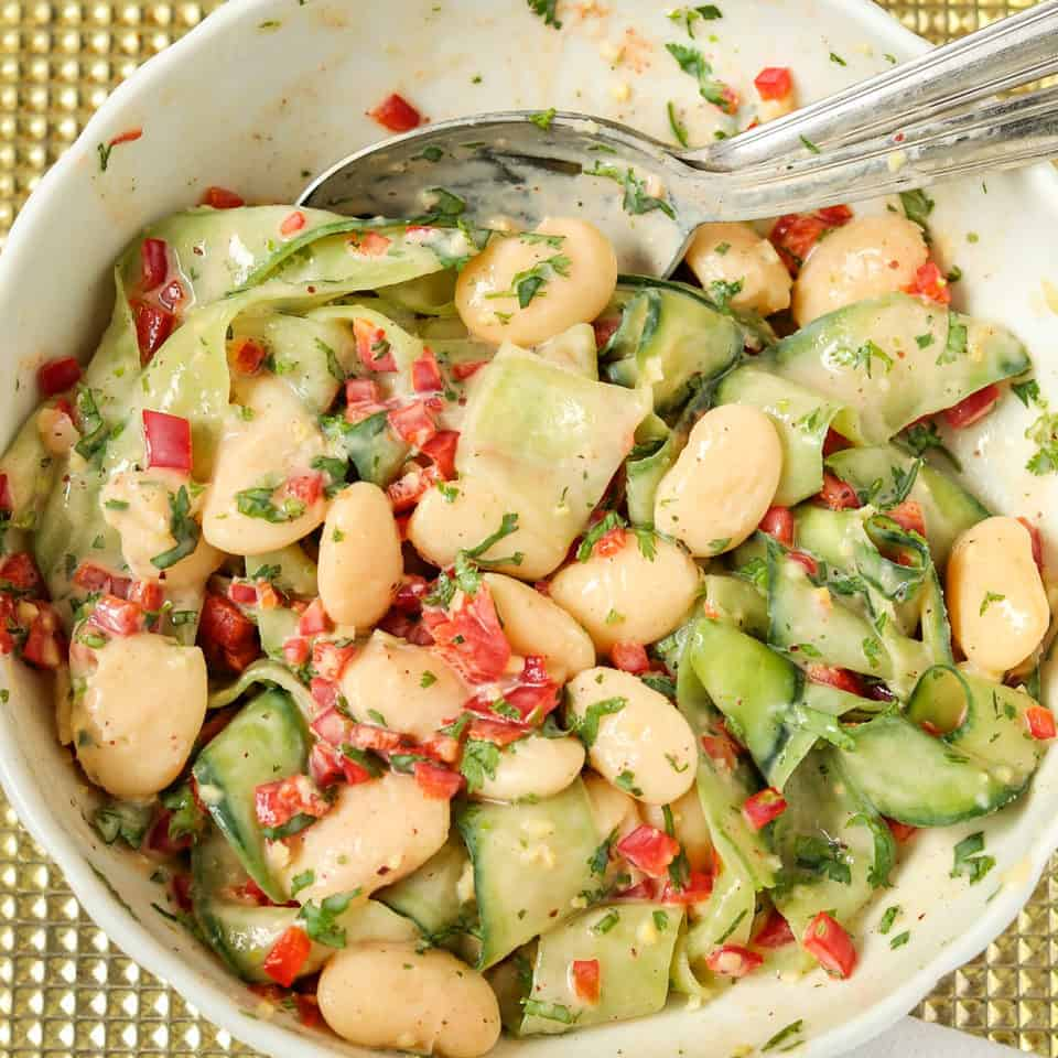 mixing butter beans cucumber salad in a bowl
