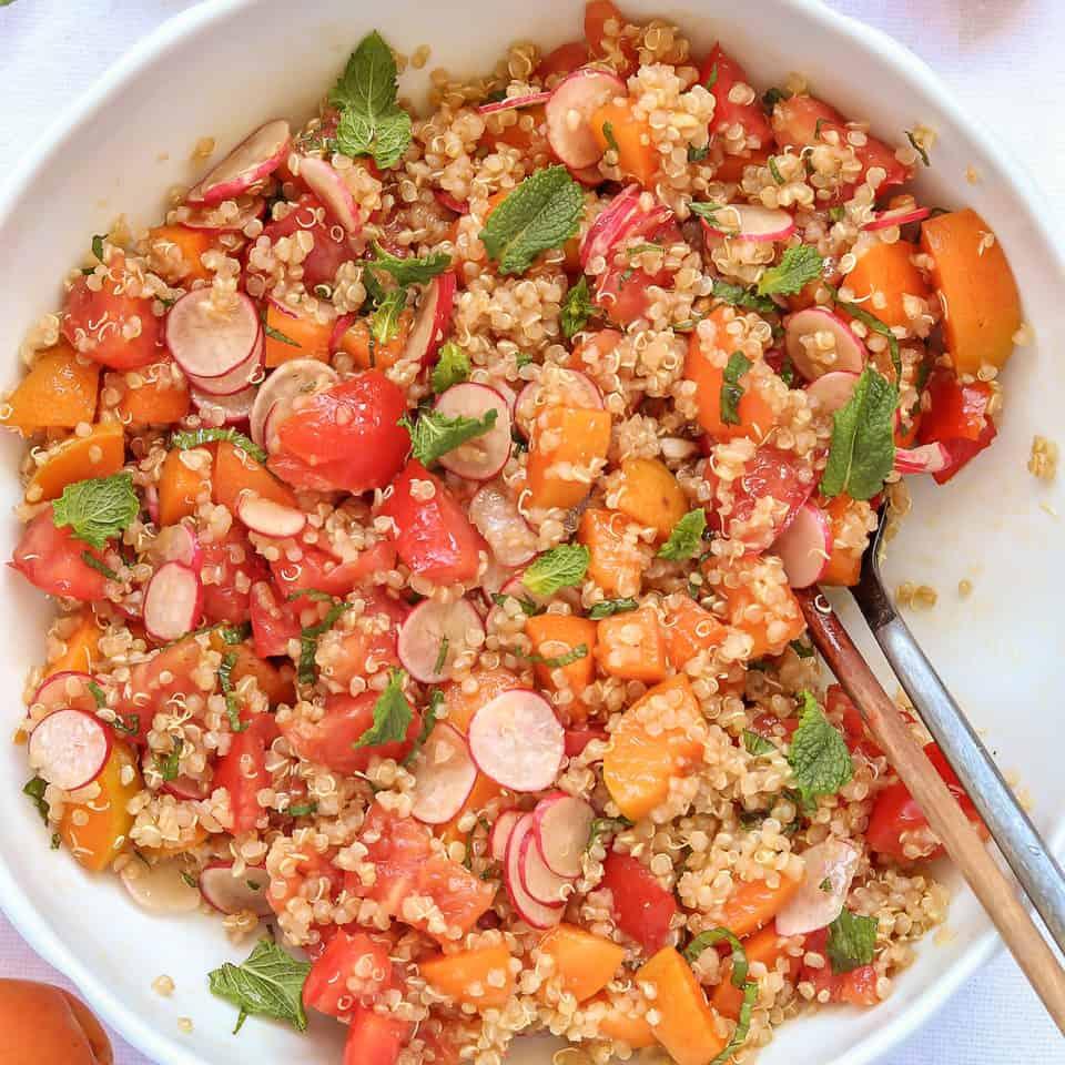 mixing quinoa apricot salad in a bowl