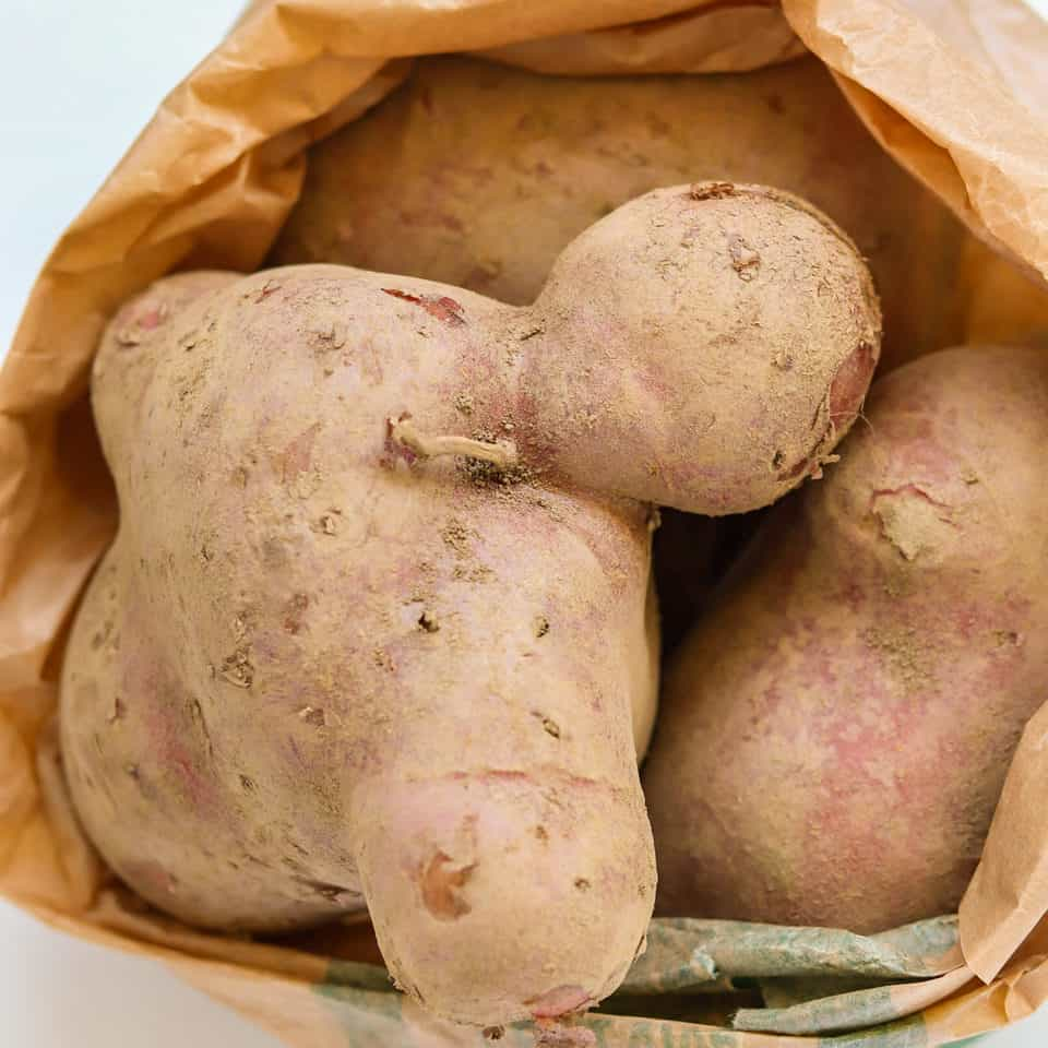huge red potatoes in a shopping bag