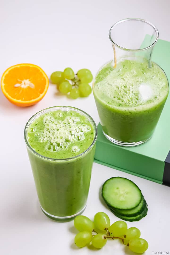Cucumber slices, orange, & grapes with a glass of cucumber smoothie