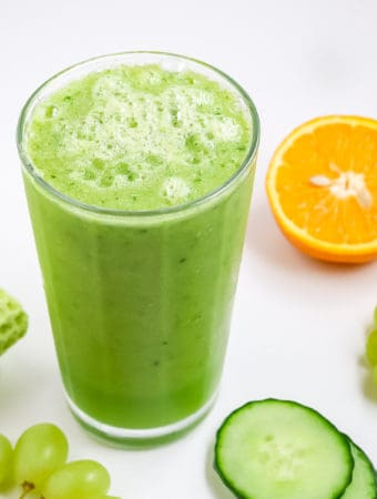 a glass of cucumber smoothie with sliced cucumbers, orange and green grapes