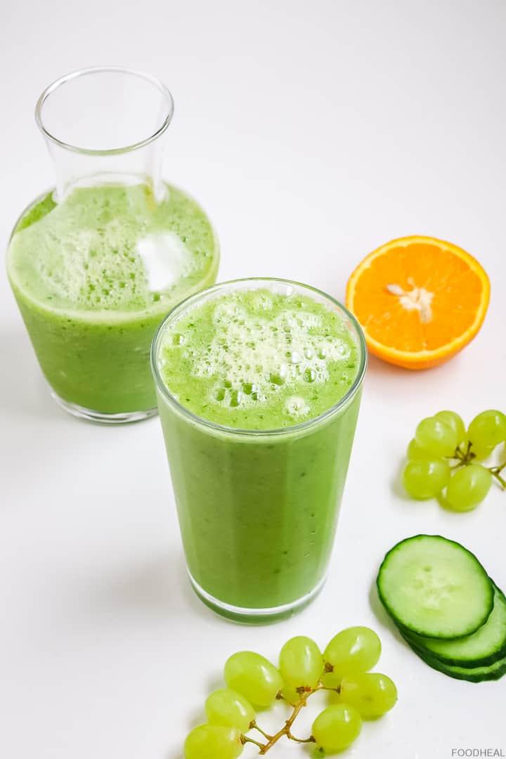 smoothie au concombre, raisins verts, demi-orange et tranches de concombre