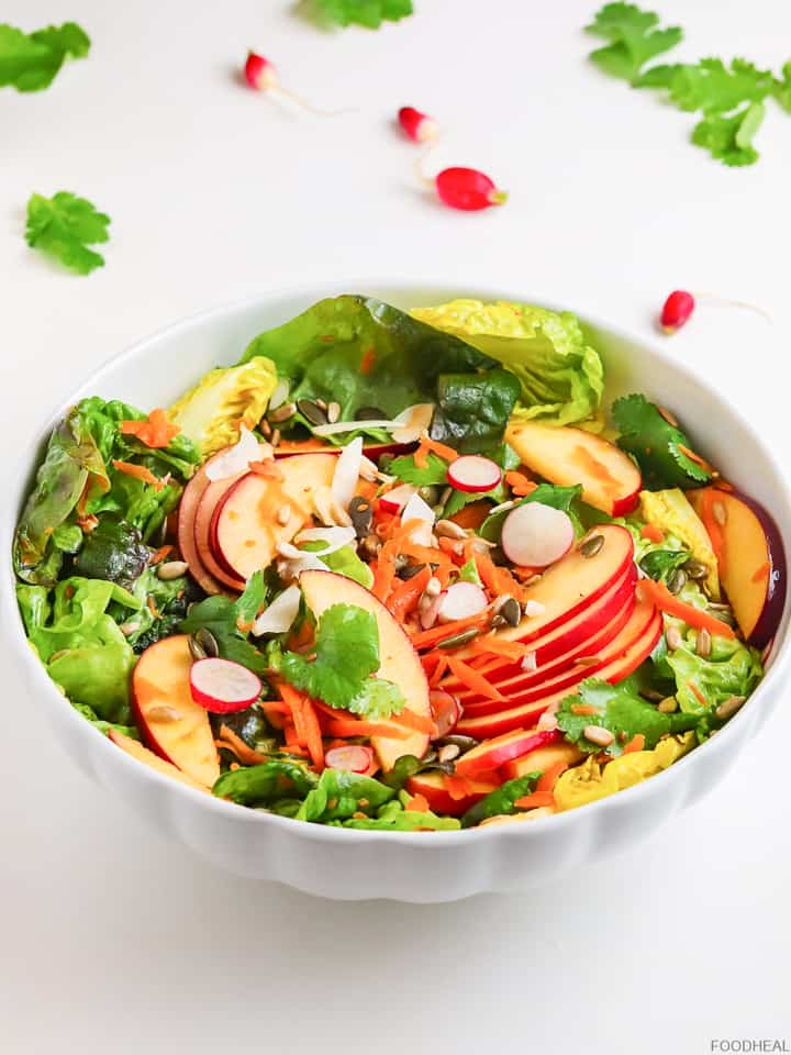 Salad bowl of apples, lettuce, seeds, coconut, radishes & cilantro