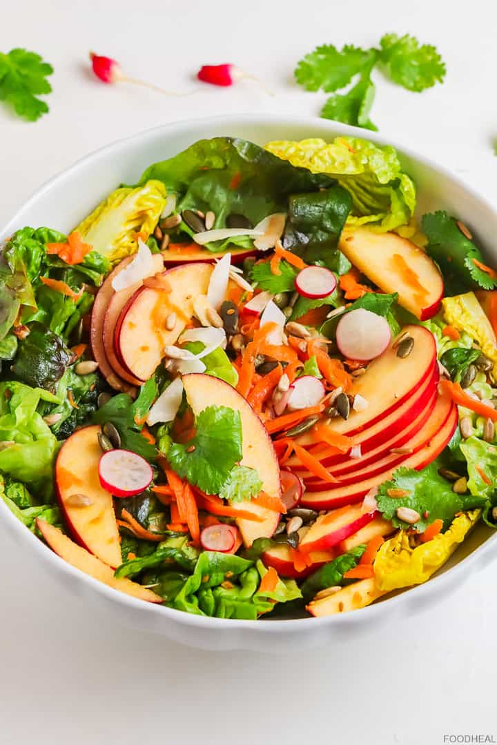 a mix of lettuce, carrot, red apples, radishes, fresh coconut and seeds salad