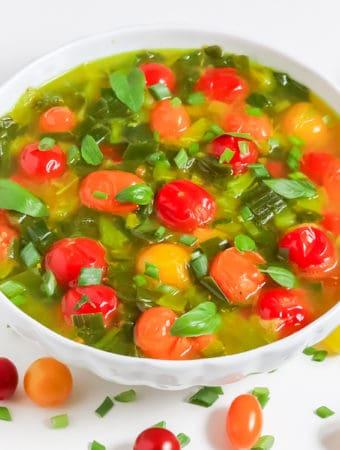 Soupe de tomates cerises d'oignon de printemps avec le basilic frais