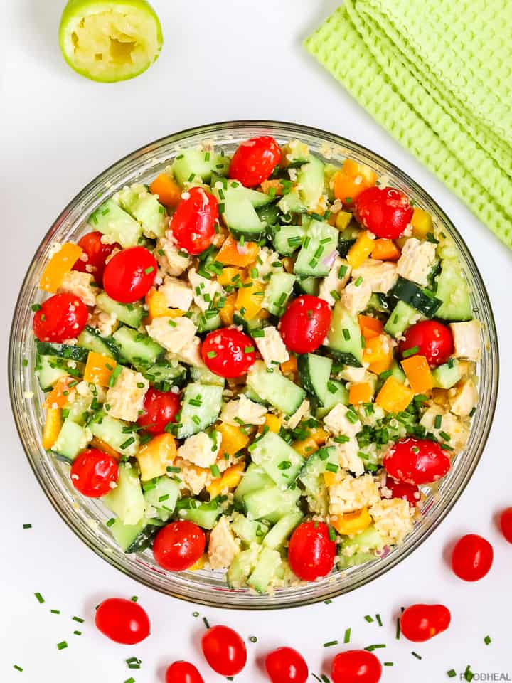 a bowl of quinoa salad with tempeh and cherry tomatoes