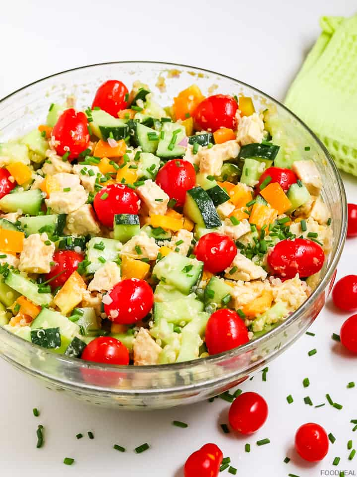 cucumber quinoa salad in a bowl with cherry tomatoes