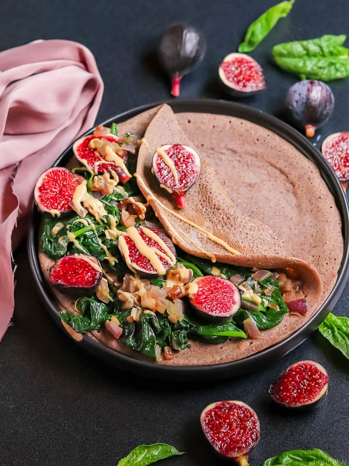 cooked spinach with figs topped with peanut butter served on a pancake
