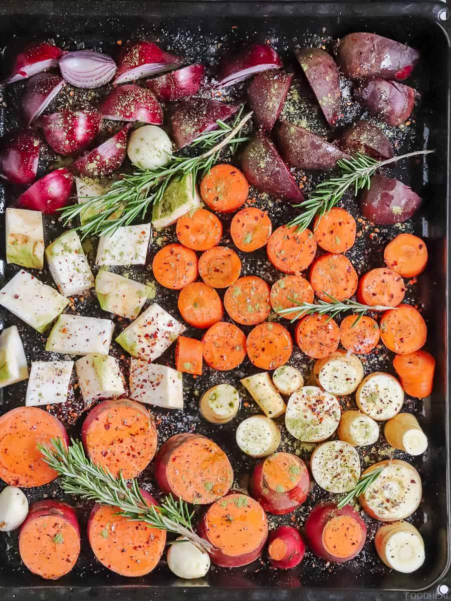 Légumes racines crus coupés épicés sur une plaque de cuisson