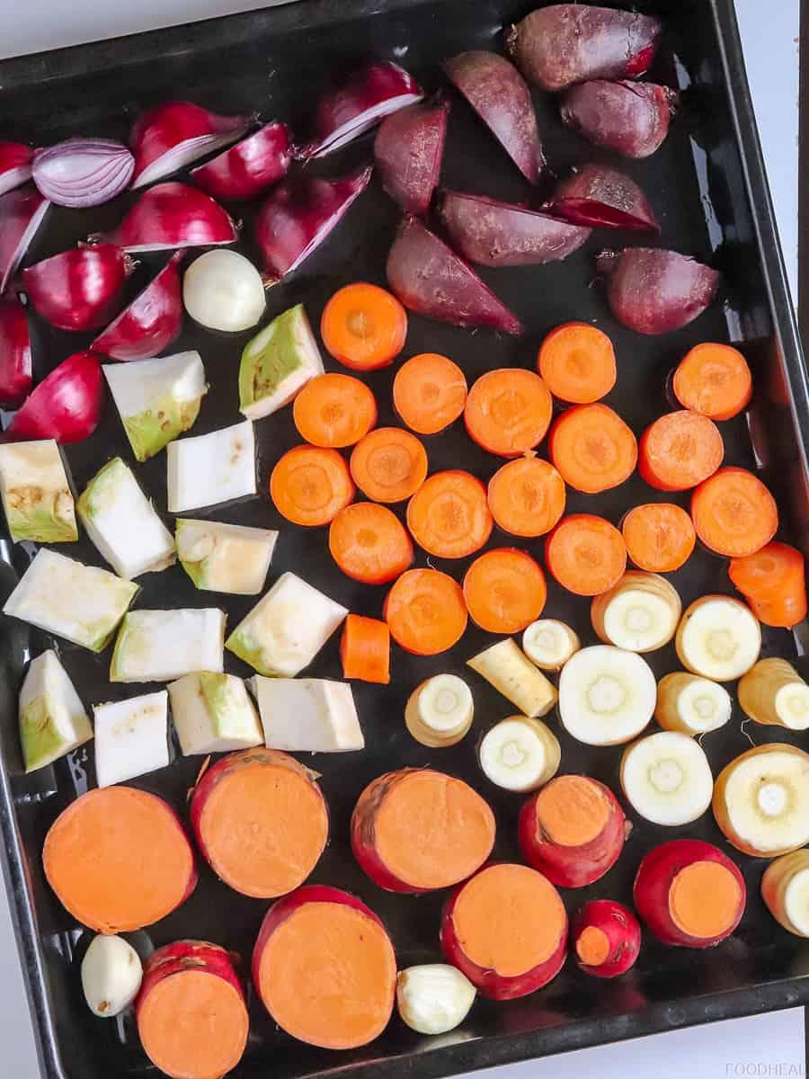 légumes racines crus coupés sur une plaque à pâtisserie