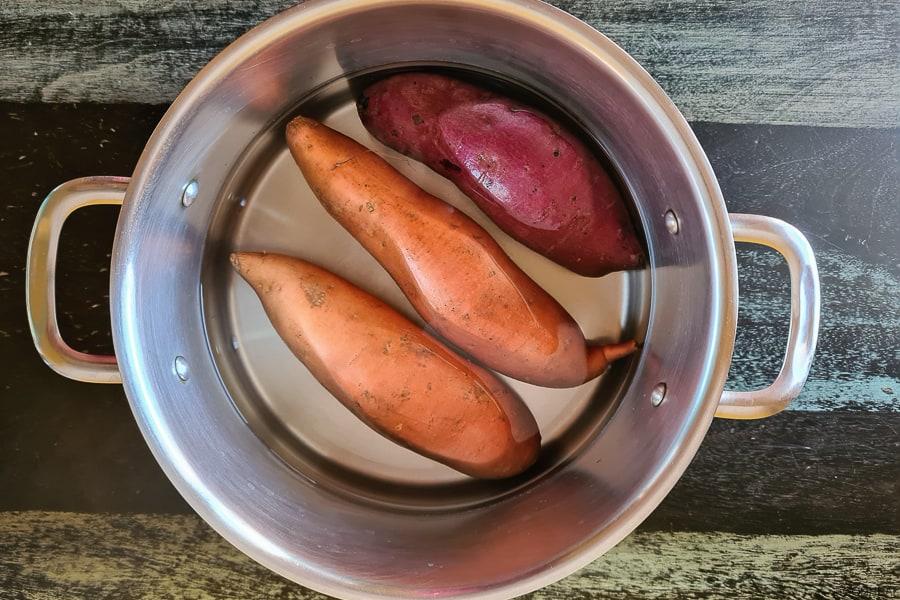 orange, purple & white potatoes in a pot