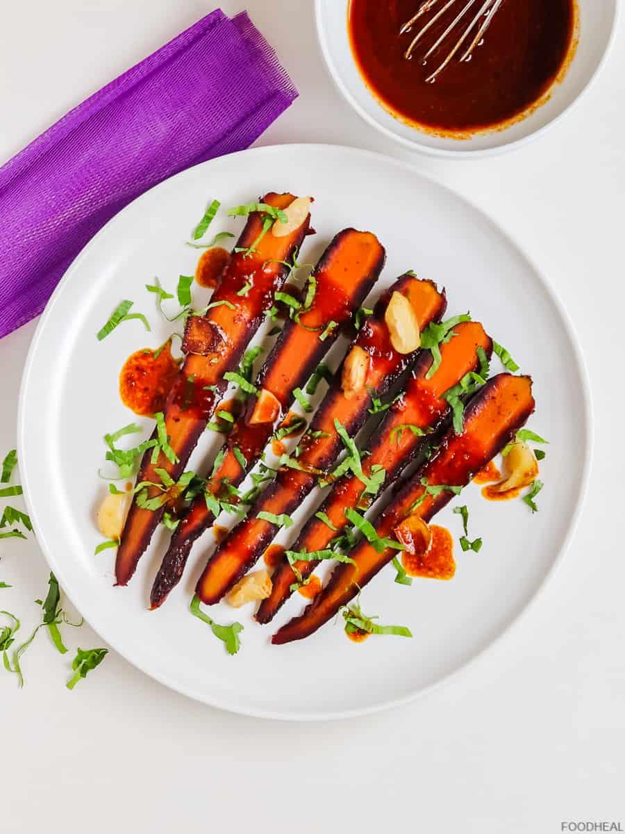 Une assiette de carottes rôties avec un bol de vinaigrette balsamique