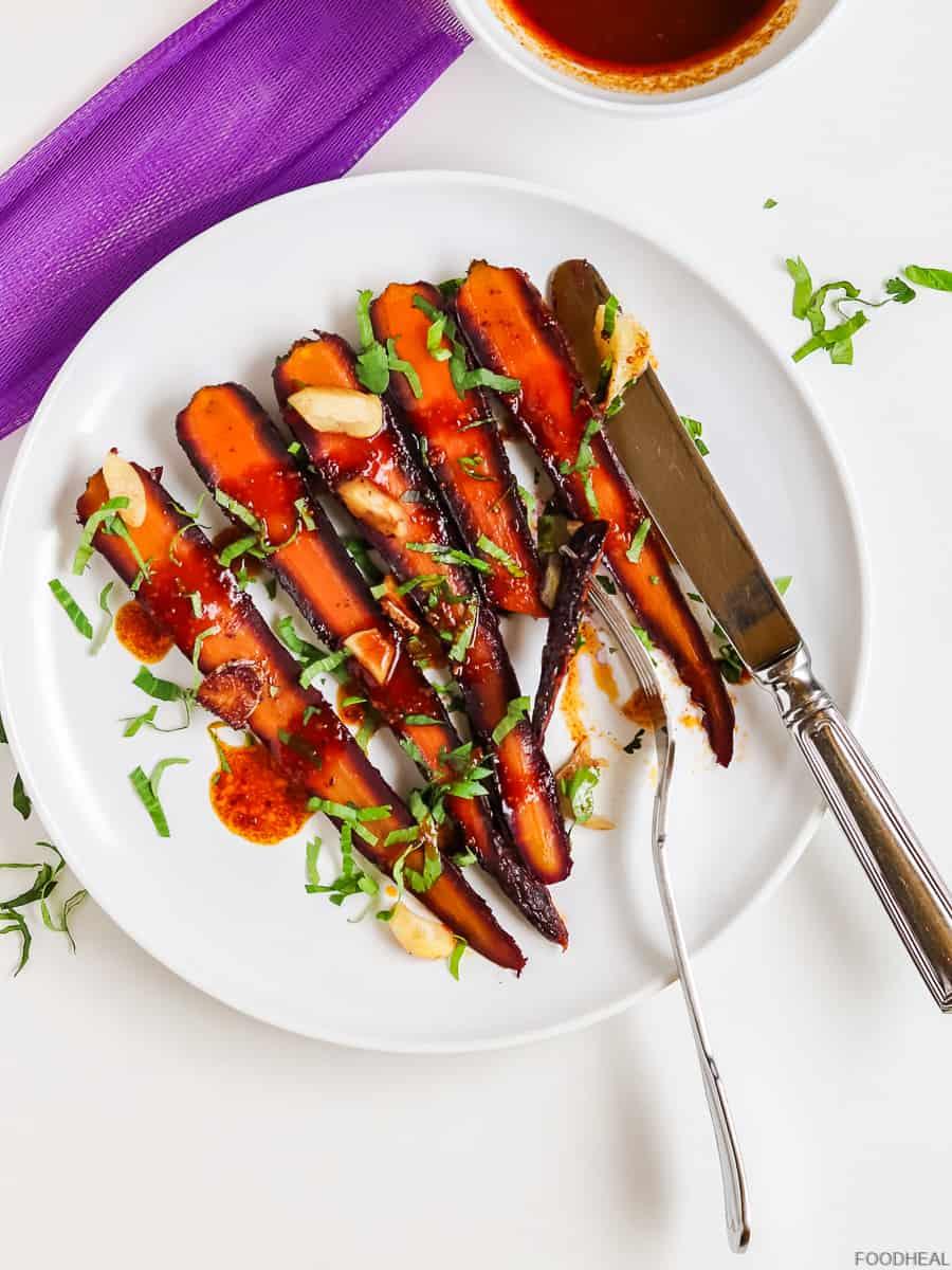 roasted carrots on a plate with a folk & a knife