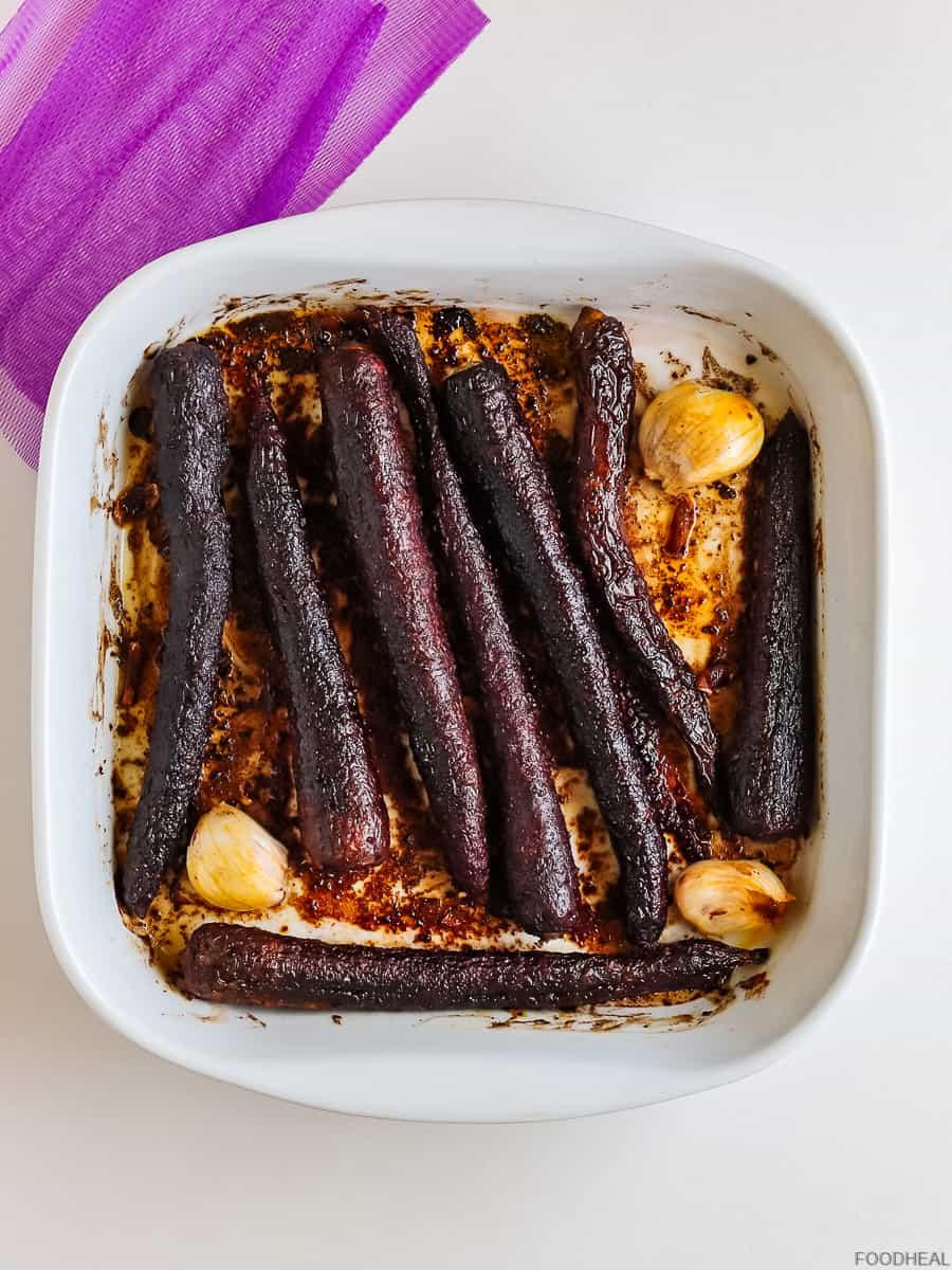 Roasted purple carrots & garlic in a baking tin